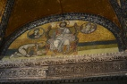 """This mosaic is above the Imperial door and shows Emperor Leo VI giving proskynesis (an act of respect) to Christ seated on the throne. Christ is blessing the Emperor and the greek words on the book held by Christ say """"Peace be with you. I am the Light of the World"""" The two pictures are of Mary and the Angel Gabriel"""